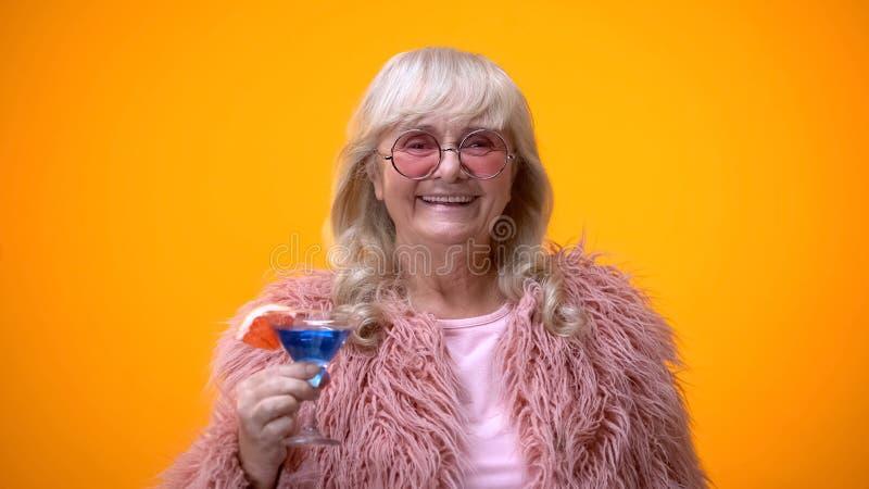 Жизнерадостная пожилая дама в смешном розовом обмундировании выпивая голубой коктейль, позитв возраста стоковые изображения