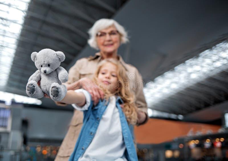 Жизнерадостная постаретая дама обнимает ее внука на современном стержне стоковая фотография rf