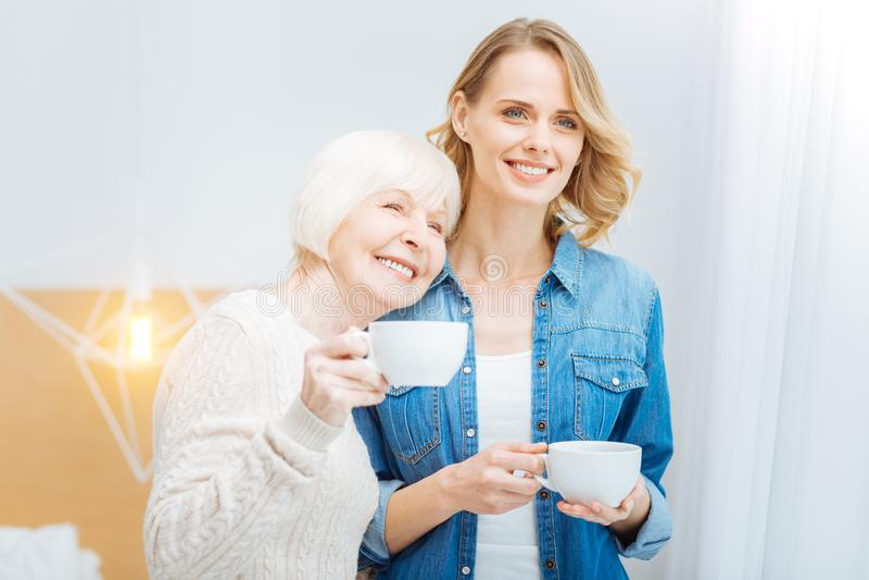 Жизнерадостная постаретая женщина полагаясь к ее внучке пока стоящ с чашкой стоковая фотография rf