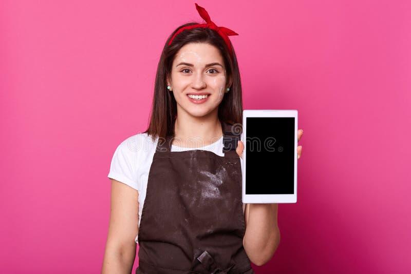 Жизнерадостная приятная девушка брюнета стоит и представляет белый планшет, выглядит счастливой, портрет изолированный студией те стоковое изображение rf