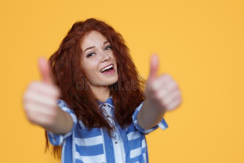 Жизнерадостная рыжеволосая женщина показывая жестами большой палец руки-вверх стоковые изображения