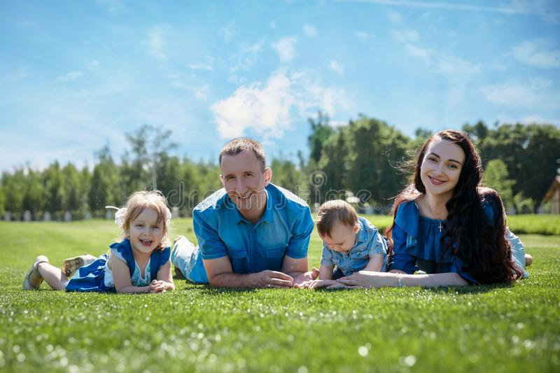 Жизнерадостная семья в парке, родители и их 2 дет лежат на траве Съемка с пирофакелом стоковое фото rf