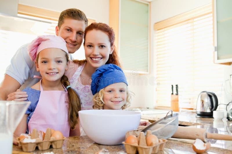 Жизнерадостная семья подготовляя тесто стоковые изображения rf