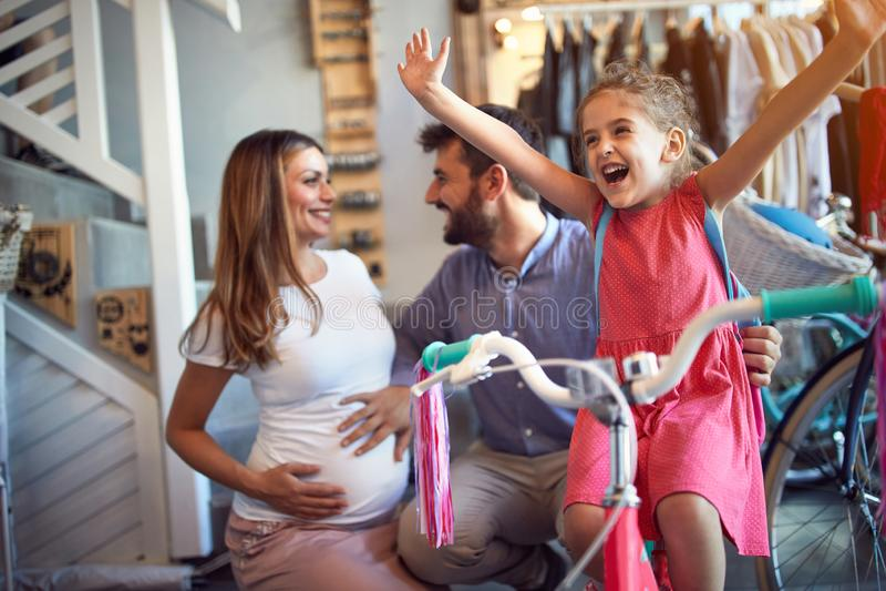 Жизнерадостная семья покупая новый велосипед для счастливой девушки  стоковые фотографии rf