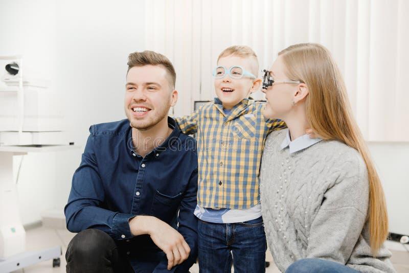 Жизнерадостная семья с небольшим офтальмологом доктора приема ребенка используя стекла стоковые фотографии rf