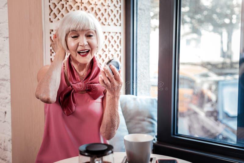 Жизнерадостная симпатичная старшая женщина в блузке шелка и с ярким макияжем стоковое фото