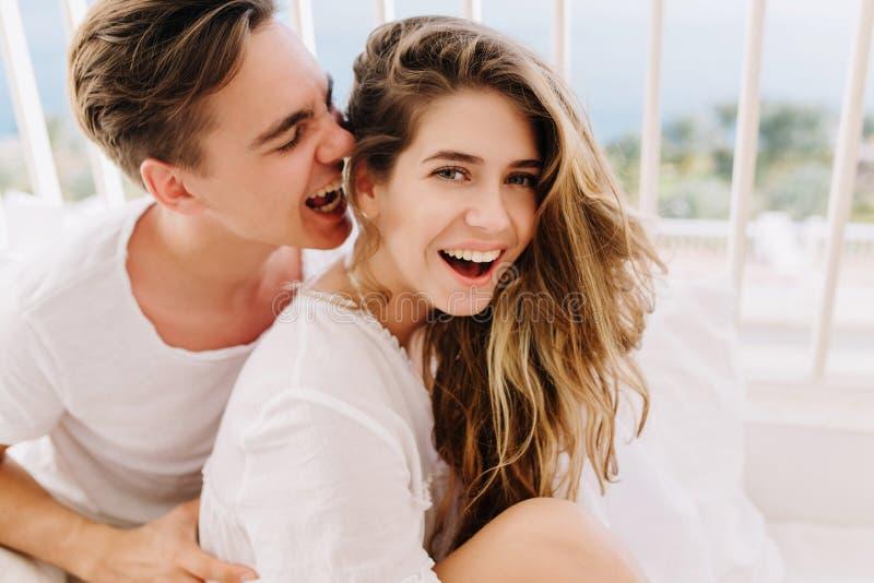Жизнерадостная смеясь девушка с ультрамодным стилем причесок имея потеху с супругом в белой одежде в воскресение утром Красивые п стоковые фотографии rf