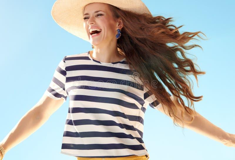 Жизнерадостная современная женщина в соломенной шляпе против скакать голубого неба стоковые фотографии rf