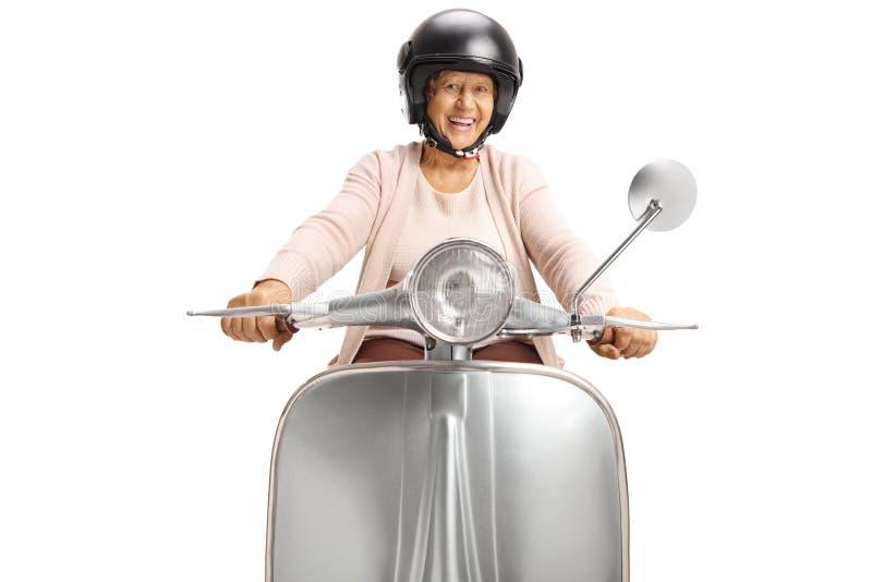 Жизнерадостная старшая женщина со шлемом ехать винтажный скутер стоковые изображения rf