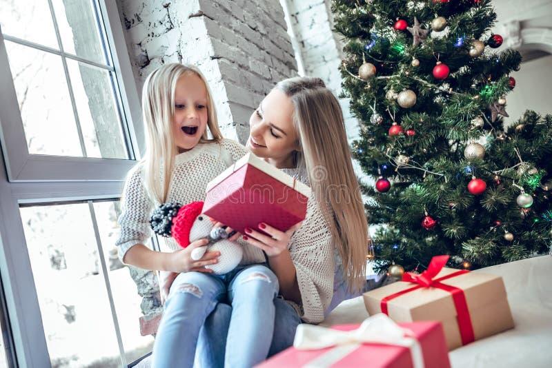 Жизнерадостная счастливая женщина с дочерью сидя на поле в живущей комнате около рождественской елки стоковые фотографии rf
