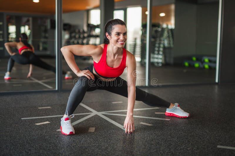 Жизнерадостная sportive женщина делая бортовые выпады стоковое изображение rf