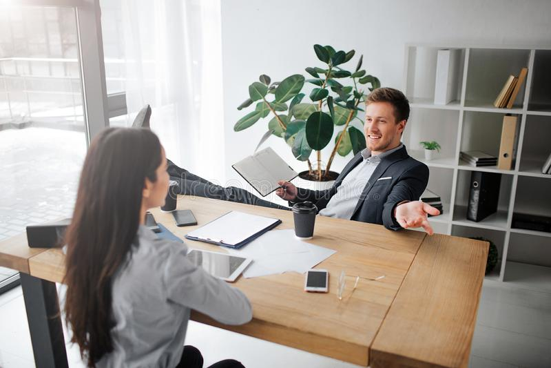 Жизнерадостное изображение счастливого молодого человека сидя на таблице и разговаривать с красивой моделью Она слушает его Ноги  стоковое фото