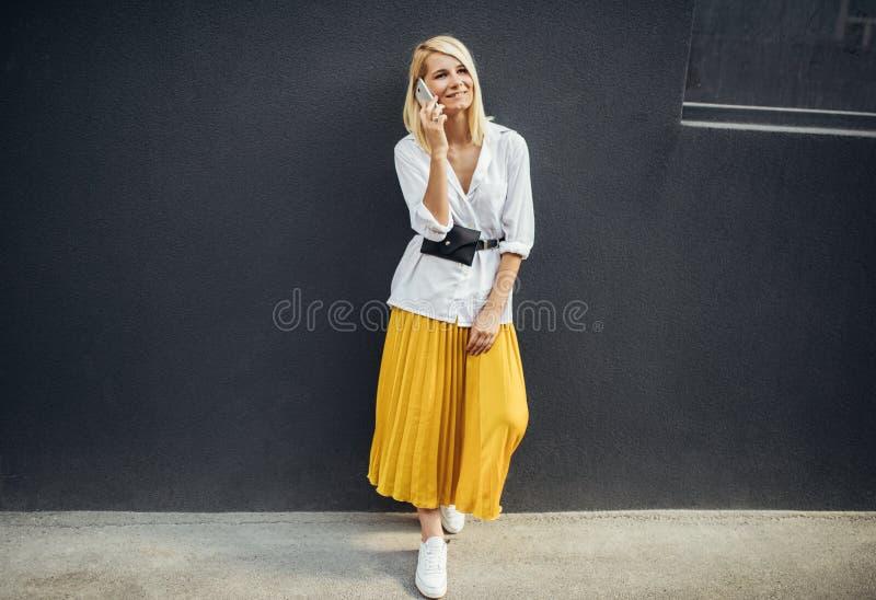 Жизнерадостное положение бизнес-леди рядом с серой стеной пока говорящ по умному телефону Милая женщина студента носит случайное  стоковое фото rf