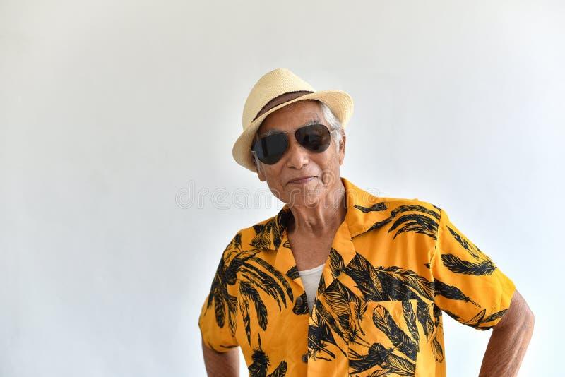 Жизнерадостные азиатский старший старик, уверенный и усмехаться престарелый с солнечными очками в красочной рубашке Гавайских ост стоковое изображение rf