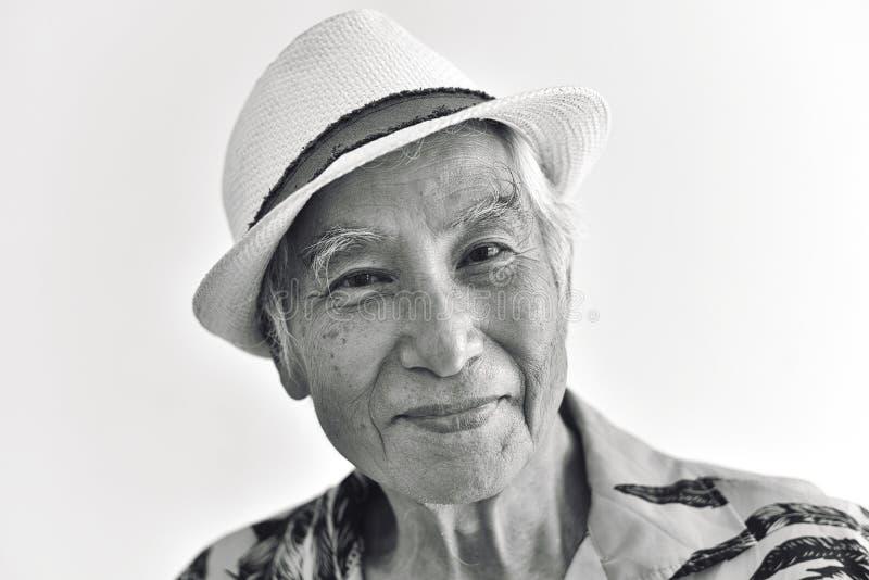 Жизнерадостные азиатский старший старик, уверенный и усмехаться престарелый с солнечными очками в красочной рубашке Гавайских ост стоковые фотографии rf