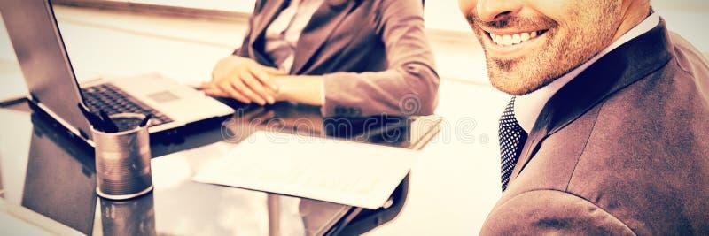 Жизнерадостные бизнесмены работая на компьтер-книжке во время встречи стоковые изображения