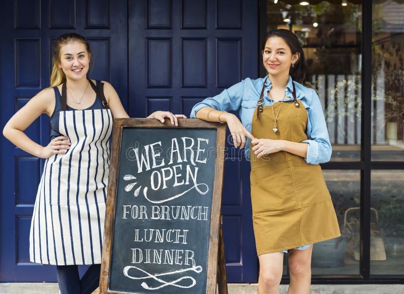 Жизнерадостные владельцы бизнеса стоя с открытым классн классным стоковые фото