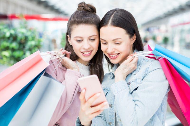 Жизнерадостные девушки используя онлайн ходя по магазинам app стоковое изображение