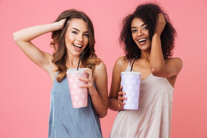 Жизнерадостные детеныши 2 женщины выпивая коктеили стоковые фото