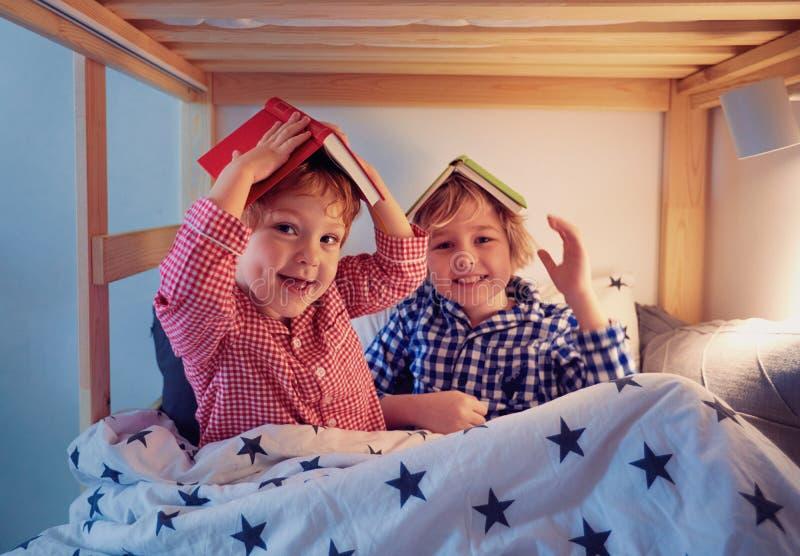 Жизнерадостные дети, братья имея потеху, играя с книгами на двухъярусной кровати во время времени ложиться спать стоковое фото