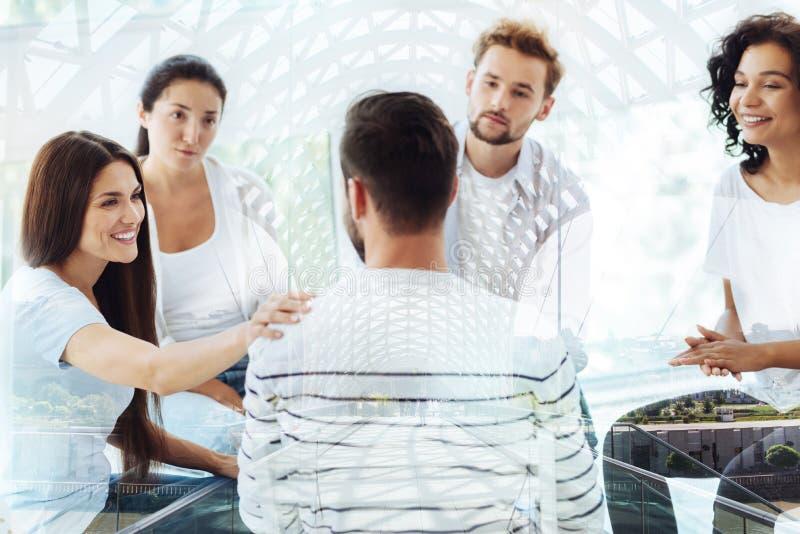 Жизнерадостные друзья сидя в офисе психологов стоковые фотографии rf