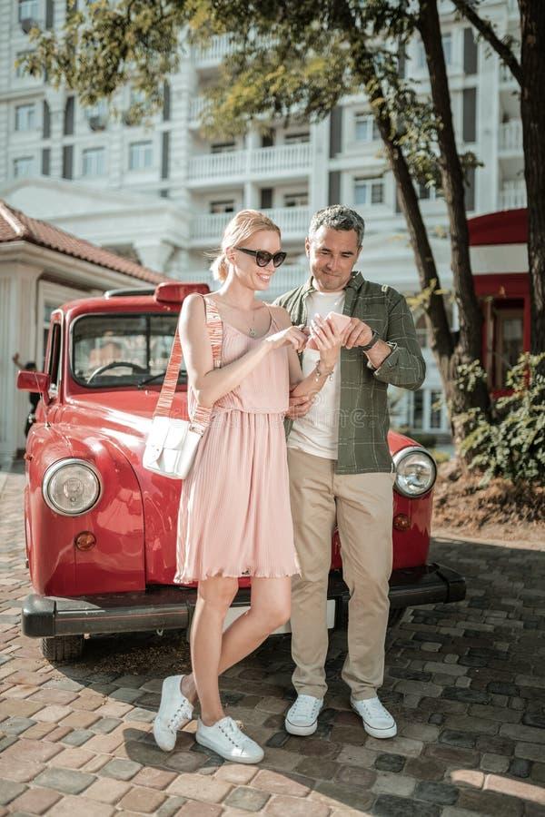 Жизнерадостные женатые пары используя смартфон совместно стоковые фото