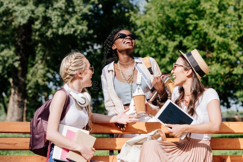 Жизнерадостные женщины отдыхая на стенде в парке совместно стоковое фото rf