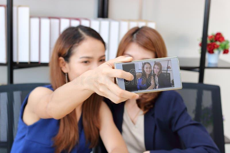 Жизнерадостные молодые азиатские бизнес-леди принимая изображение или selfie совместно в офис стоковые фото