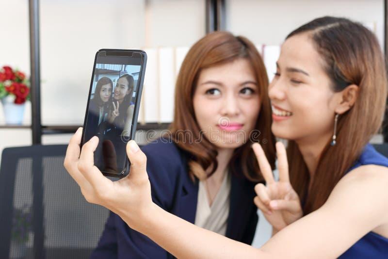 Жизнерадостные молодые азиатские бизнес-леди принимая изображение или selfie совместно в офис стоковая фотография rf