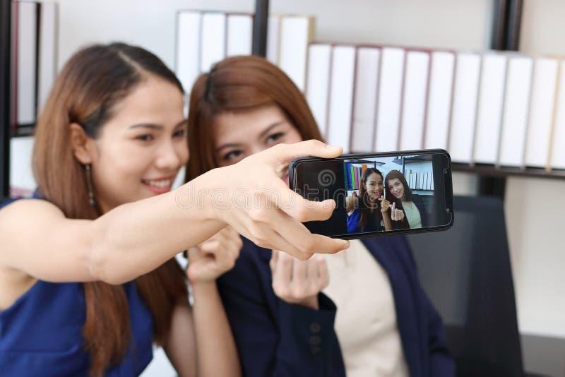 Жизнерадостные молодые азиатские бизнес-леди принимая изображение или selfie совместно в офис стоковое фото rf