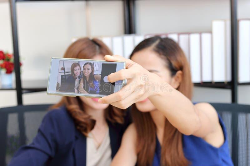 Жизнерадостные молодые азиатские бизнес-леди принимая изображение или selfie совместно в офис стоковое фото