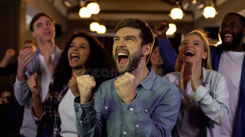 Жизнерадостные молодые люди радуясь победа команды, профессиональное достижение команды стоковые изображения