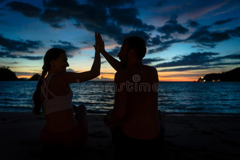 Жизнерадостные молодые пары давая максимум 5 пока сидящ на тропическом пляже стоковые фотографии rf