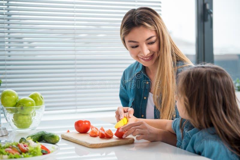 Жизнерадостные овощи вырезывания матери вместе с ее ребенком стоковое изображение