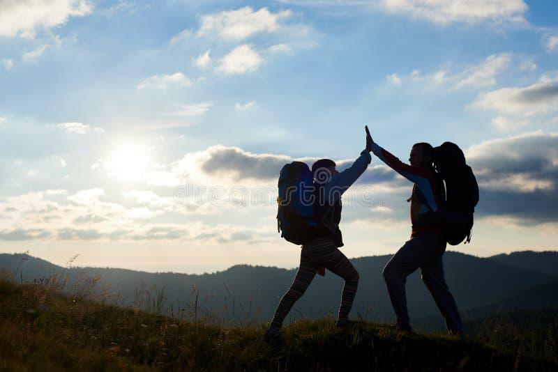 Жизнерадостные пары с рюкзаками na górze горы дают один другого высоко 5 против захода солнца стоковые изображения