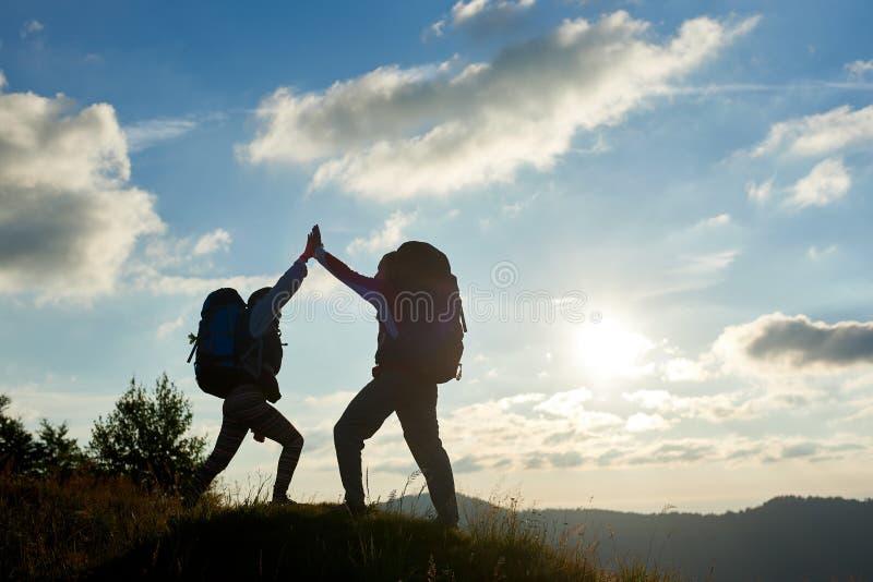 Жизнерадостные пары с рюкзаками na górze горы дают один другого высоко 5 против захода солнца стоковое изображение