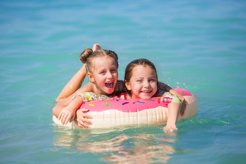 Жизнерадостные подруги плавают на круг на море стоковая фотография
