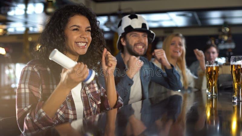 Жизнерадостные поклонники футбола поддерживая любимую команду в пабе, людей и женщин празднуя стоковые изображения