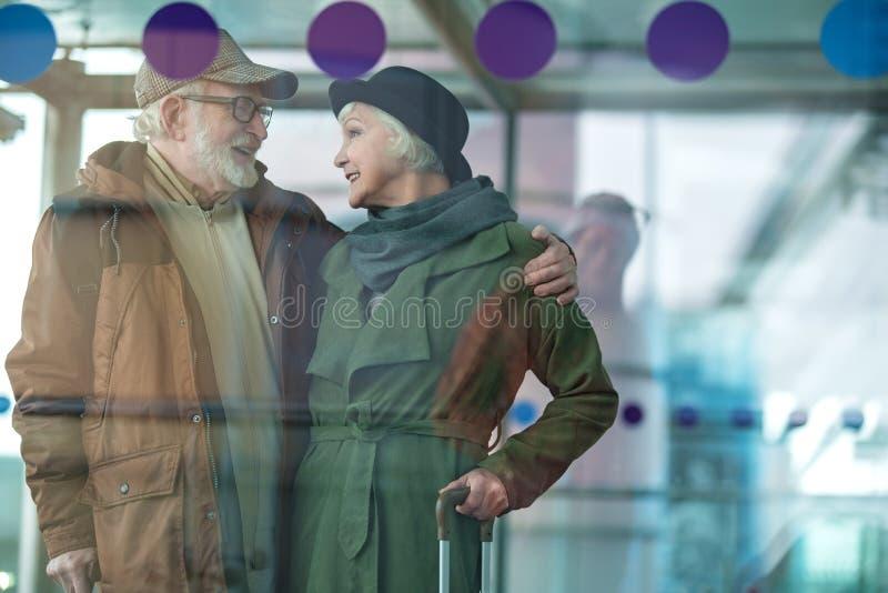 Жизнерадостные старшие дама и джентльмен обнимают с счастьем стоковая фотография
