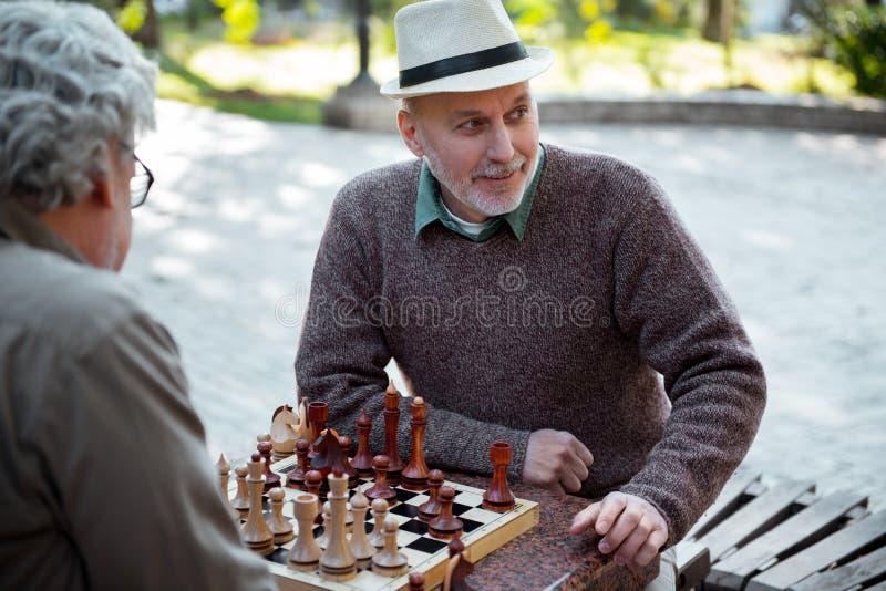 Жизнерадостные старшие друзья играя шахмат внешний стоковое изображение