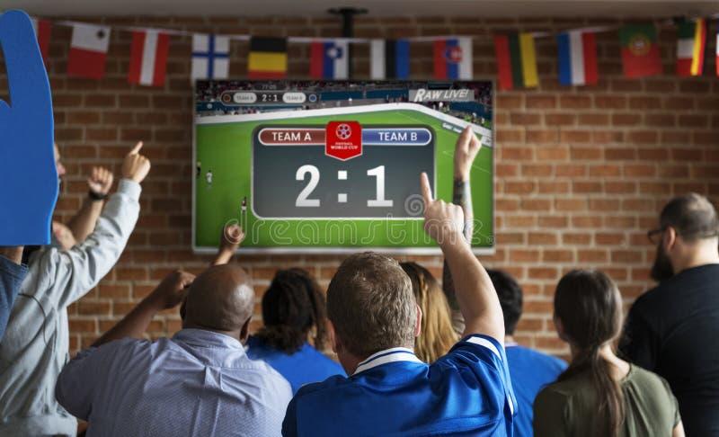 Жизнерадостные сторонники наблюдая футбол на пабе стоковая фотография rf