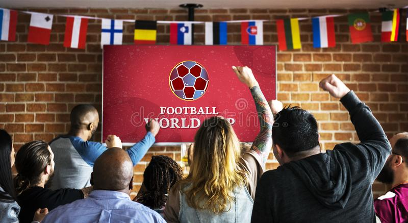 Жизнерадостные сторонники наблюдая футбол на пабе стоковые фото