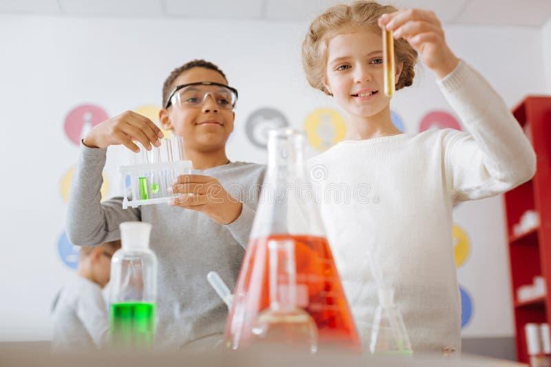 Жизнерадостные студенты проверяя результат химического эксперимента стоковое изображение rf