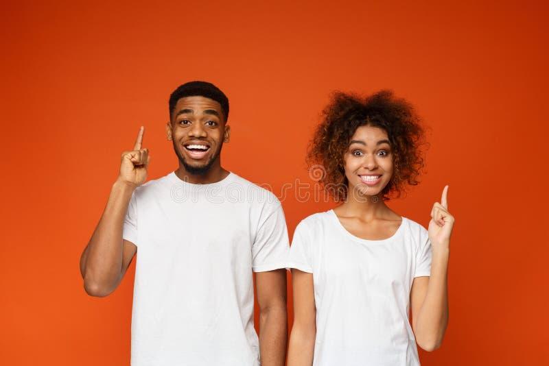Жизнерадостные указательные пальцы пункта человека и женщины вверх стоковая фотография rf