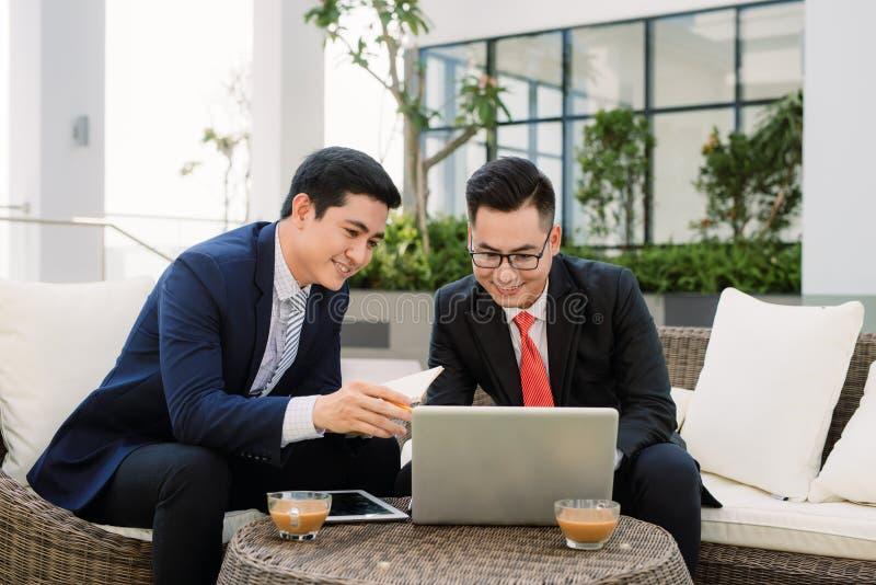 Жизнерадостные умные бизнесмены обсуждая их проект стоковое фото rf