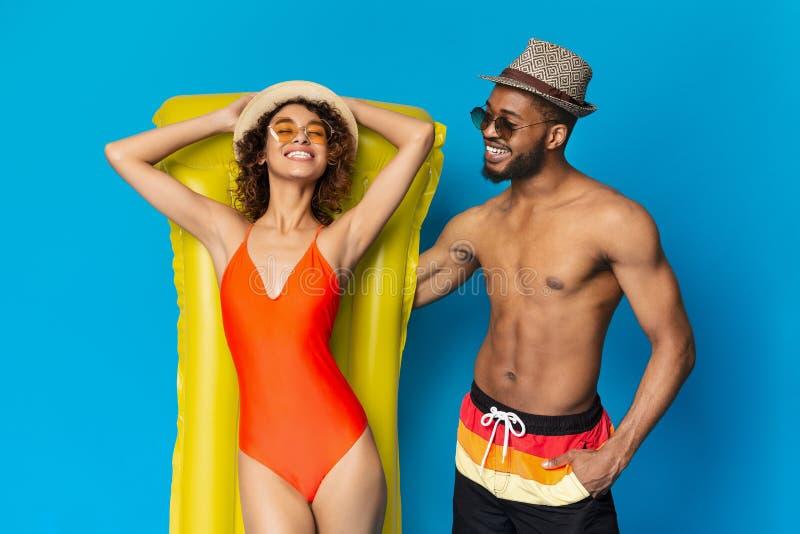 Жизнерадостные черные пары отдыхая с плавая тюфяком стоковые фото