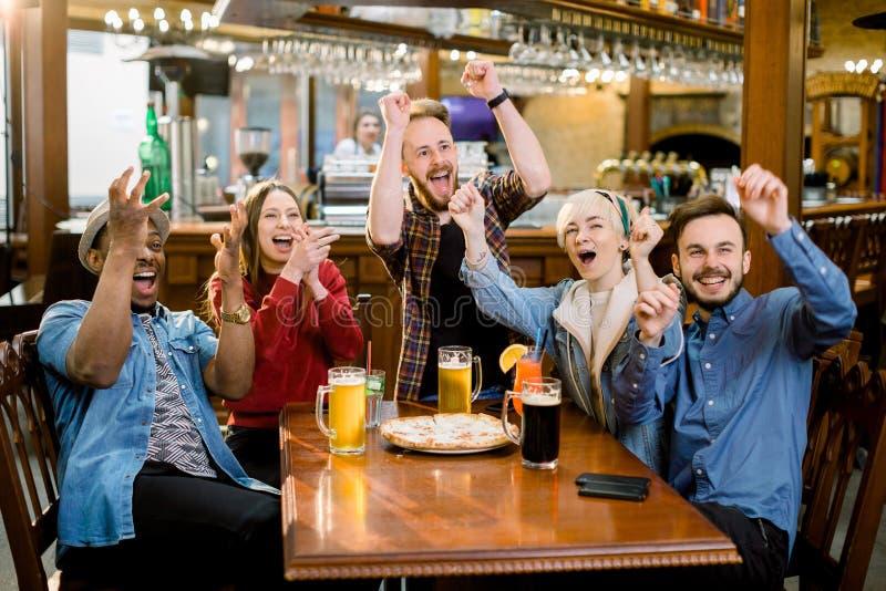 Жизнерадостные multiracial друзья имея потеху есть в пиццерии Они наблюдают футбольный матч эмоционально стоковое фото rf