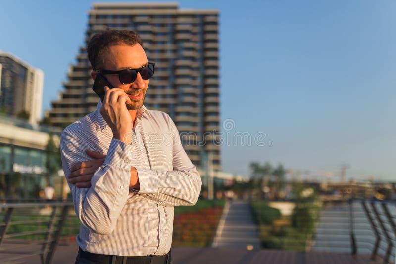 Жизнерадостный бизнесмен говоря на смартфоне outdoors стоковые фото