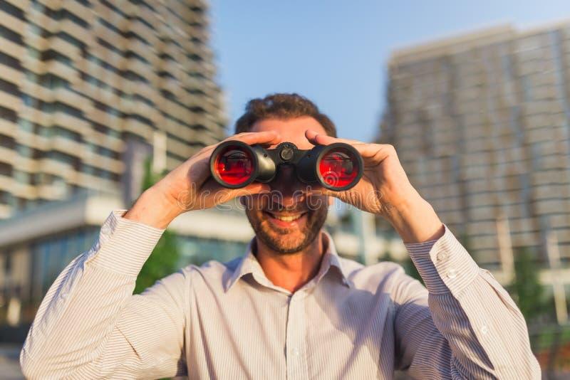 Жизнерадостный бизнесмен держа бинокли Концепция зрения дела стоковое изображение