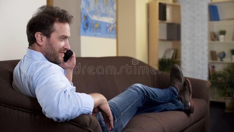 Жизнерадостный взрослый мужчина беседуя с другом по телефону, сидя на софе дома стоковая фотография
